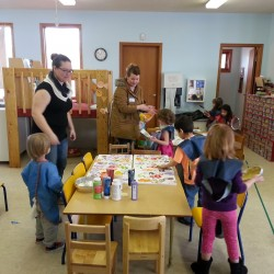 Parents supervising children while they paint pictures for the teachers